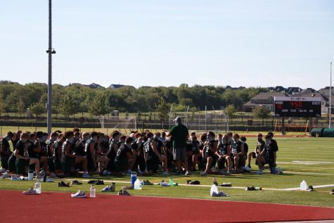 Football players kneel at the end of practice while their coach talks. The Big 10 and Pac-12 conferences announced their football season will be cancelled for the 2020 fall season.