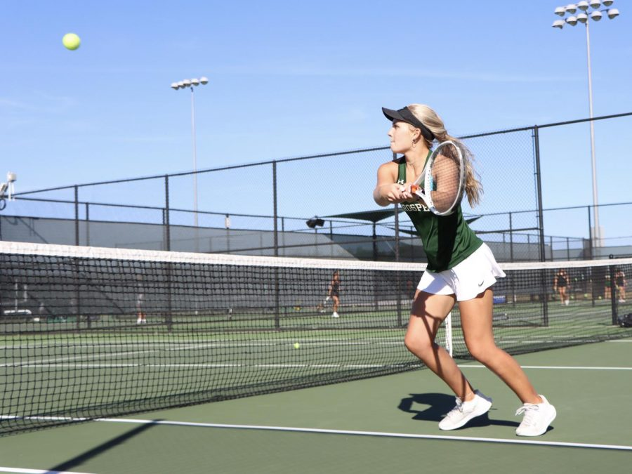 After rushing the net, senior Lauren Hallauer hits a backhand volley. Hallauer played doubles with junior Rebecca Gutierrez. The doubles team beat Denton Braswell   6-2, 6-2.