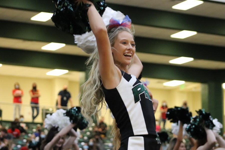 Poms in the air, senior Grace Dimmick finishes her routine. The  cheerleaders helped prepare and present the pep rally.