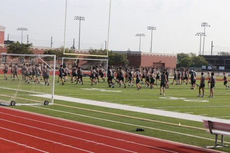 Junior varsity and varsity football teams run into the MPF to finish practice indoors. The teams walked through their plays out on the field for their games on Thursday and Friday. Both teams have practiced to play their first game of the season against Prestonwood Christian Academy.