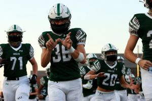Running onto the field at the start of the game, senior Brad Larson holds up a