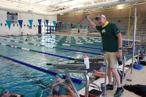 At a morning practice, head swim coach Trey Sullivan gives instruction to his athletes.