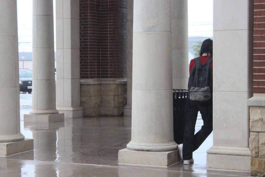 Standing in the pouring rain on Tuesday, Sept. 1, Junior Leland Nitzel waits for a friend outside the auditorium doors. The rain started during second period and continued intermittently for the rest of the day.