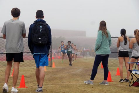 Emerging from the overcast and foggy conditions, junior Remi Oyedipe gains a lead in his competition. After getting a glimpse of the course behind him, Oyedipe continues toward the finish line.