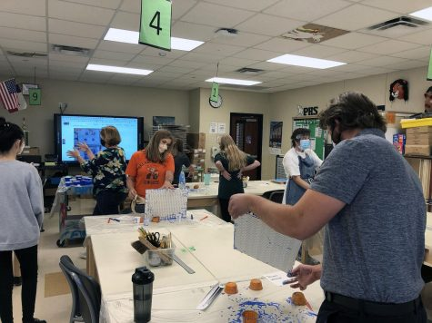 """As they swirl paint on a canvas, teachers create acrylic pour artwork in a workshop taught by National Art Honor Society students. The group held the workshop Oct. 8, and NAHS sponsor Judy Seay said she plans to hold more in the future. """"A lot of the teachers were feeling really stressed, and they commented on how they would like to do art, and they don't have time to do it,"""" Seay said. """"I thought it would be nice for us to give them an opportunity to learn something."""""""