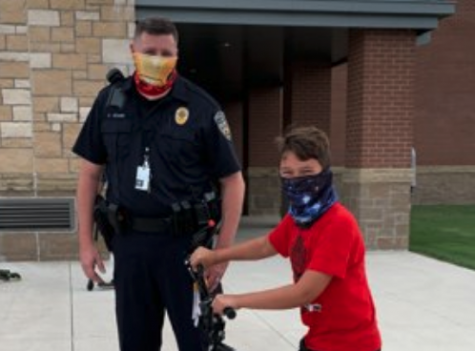 "Officer Allen Adams and Lucas Corona are spending time together infront of Furr Elementary School. this photo first appeared on PISD Twitter account on Sep. 16. ""Children these days, they need to see some positivity,"" Adams said. ""We"