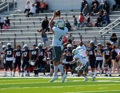 Catching a pass from his fellow teammate, outside linebacker Grant Peck, No. 6, jumps in the air. This was the Eagles' first district game.
