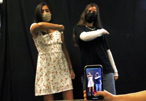 "As they perform for a recording, sophomore Gianna Galante and senior Emily Reish do a TikTok dance to ""All About That Cake"" by Nodis. In the attached article, columnist Rusty Joe Gonzales discusses how TikTok documents activism and a return of country music to ""its  original roots of letting underrepresented artists have a voice."" Besides activism, some students use the app to connect with others. ""TikTok is a nice outlet,"" Galante said. ""I really like creating videos on there for my friends and others to see."""