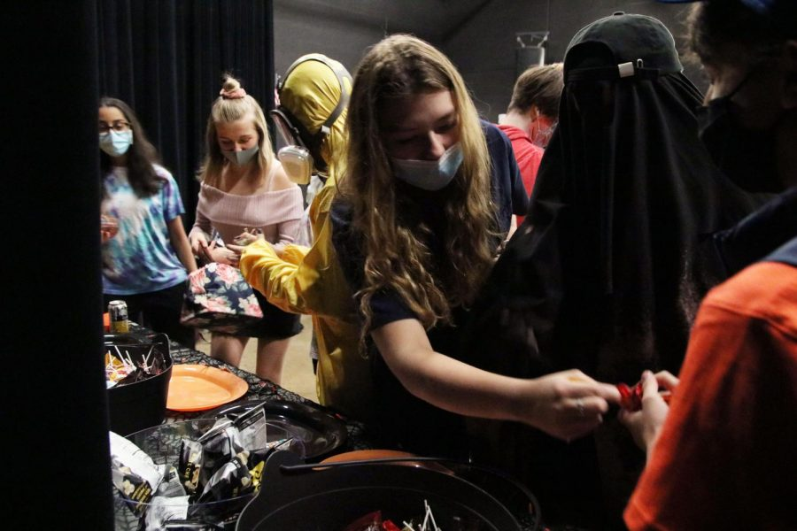 While moving around the school's Blackbox, theatre, sophomore officer Lauren Grammer and others collect candy from the snack table during the Theatre Department's Halloween Social on Wednesday, Oct. 28. This was the third social of the year, and the board of officers has plans to do more.