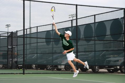 Jumping to make his serve, sophomore player Ridge Daniels hits the tennis ball above his head. This is his first year on varsity, and he currently plays mixed doubles with junior Mia Camilleri.
