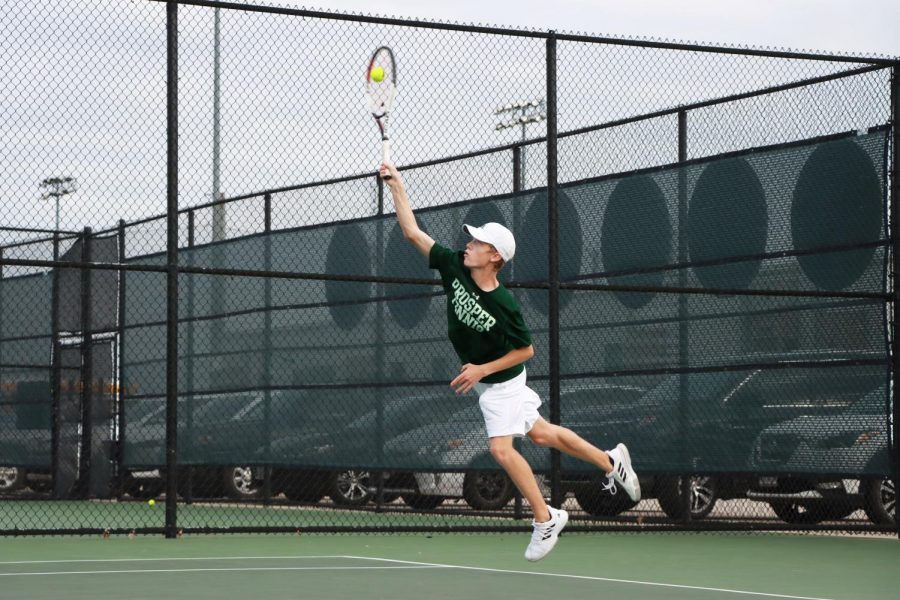Jumping to make his serve, sophomore player Ridge Daniels hits the tennis ball above his head. This is his first year on varsity, and he currently plays mixed doubles with junior Mia Camilleri. I think I played well in the match against Braswell, Daniels said. I just went out and played my game with confidence and stayed relaxed.