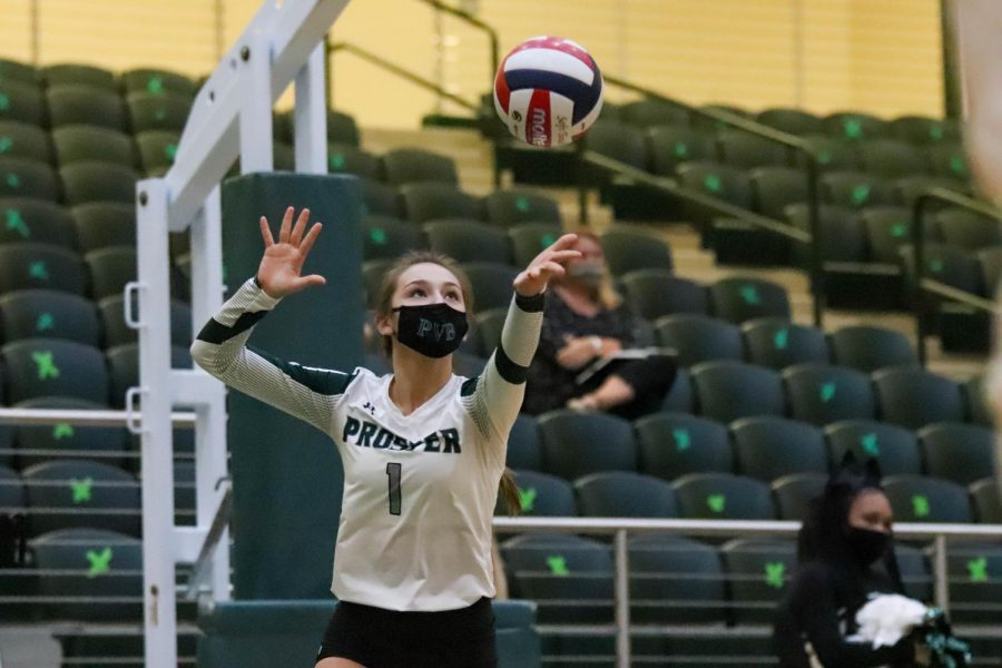 Ball in the air, sophomore Callie Kieffer starts her serve. Kieffer made 23 assists. This is her first year on the varsity team.