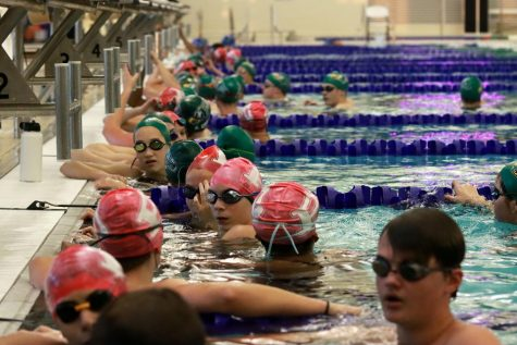 Gathered at the ends of their lanes, swimmers await warm-up instructions from their coach. Warm ups began at 6 p.m., and the meet started at 7 p.m. on Wednesday, Oct. 21. Prosper competed against Plano West High School at the meet, losing to the Plano West girls team by three points, and their boys team by 27.