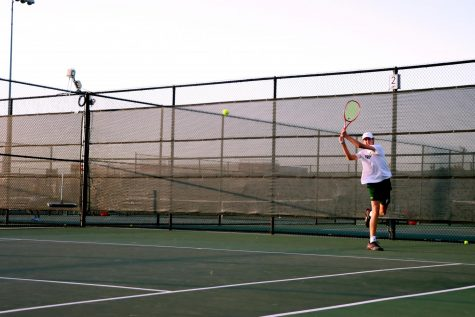 Following through on his backhand, junior Drew John returns his opponent
