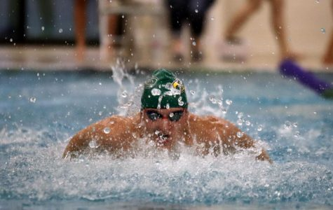 Coming out of the water for a breath, junior Scott Fredrick moves down his lane during his 100-yard butterfly event.
