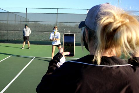 """Assistant tennis coach Hollie Cunningham films head tennis coach Mandy Weaver and athletic trainer Michael Henry in a TikTok. Weaver and Henry have set a tradition to make a new TikTok every Friday. In the attached feature, sports editor Caroline Wilburn highlights coach Marco Regalado from Eaton High School, who takes the same approach as Weaver and Henry. """"Coach Henry and I have always had office pranks that we"""