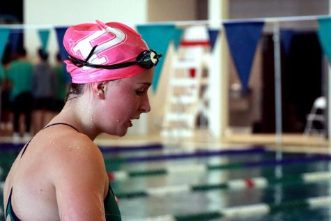 After diving in for the 200-yard freestyle relay, freshman Jaeda Crabtree claps for the rest of her relay teammates as they compete. Crabtree, and other swimmers, wore pink swim caps throughout the month of October as a way to bring awareness to breast cancer, and show support for those affected by the disease.