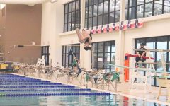 Tucking into her dive, sophomore Shaelyn Haiman spins upside down during the dive portion of the meet against Rock Hill and Frisco's Memorial High. The divers competed at 5:30 p.m. while the swim teams began at 7 p.m. This marked the team's sixth meet.