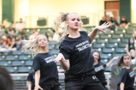 "Using ""sass,"" senior Zoë Dale starts off her routine. The Talonettes practice daily to do precise performances throughout the year. ""I was incredibly proud of the Talonettes regarding our active schedule with the field performance, pep rally, and tedious hours we had put in for practice"" Dale said. ""Though we were upset for the original homecoming pep rally being pushed forward, we found the positive and really pulled through as a whole and performed with such passion."""