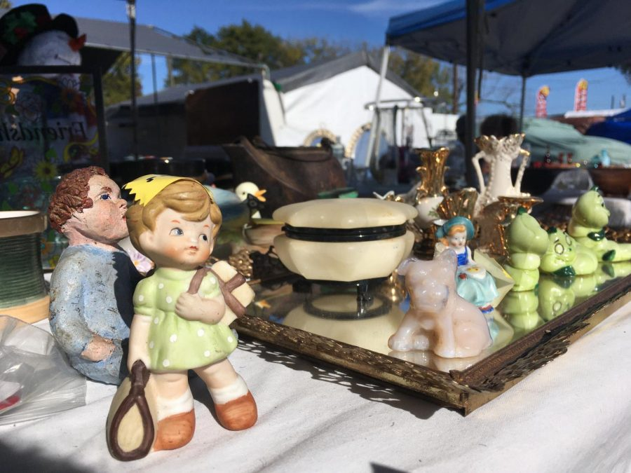Sweet trinkets and figurines are presented neatly on this seller's table. Sunlight reflects off of the glass mirror that some of the items are placed on.