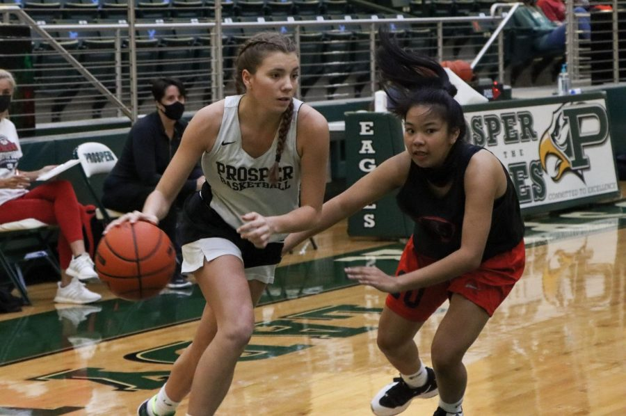 Changing directions to avoid her opponent, junior Hayden Nichols dribbles her way towards the basket. Nichols plays as a point guard and a shooting guard for Prosper's girls varsity team.