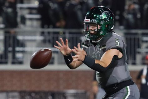 "Holding his hands out, quarterback Jackson Berry positions himself to catch the ball. Berry, a senior, has played on the varsity team since his freshman year. ""I just need to read the defense a little bit better,"" Berry said. ""I feel like a couple sets, a couple things I didn"
