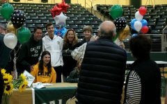 Celebrating her signing day with family, senior Taylor Youtsey sports her gold sweatshirt. Youtsey signed to play volleyball for Cal Poly.