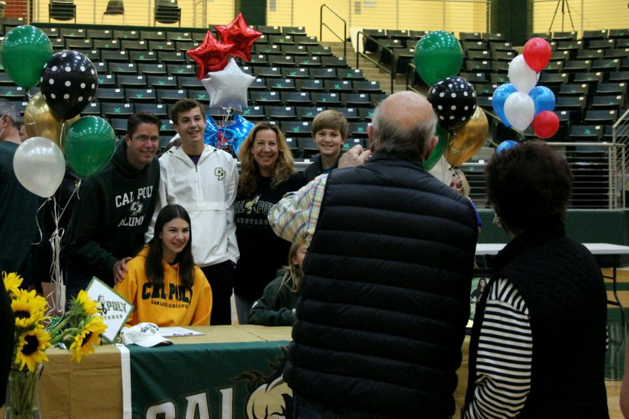 """Celebrating her signing day with family, senior Taylor Youtsey sports her gold sweatshirt. Youtsey signed to play volleyball for Cal Poly. """"I think it was really cool to see all of the athletes and to recognize all of their hard work,"""" Youtsey"""