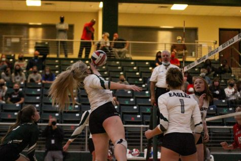 Jumping to the ball, junior Kendall Hewitt attempts to pass the ball over the net. After this weeks win, the team is now 11-1 in district play.  Overall, they are 13-2.