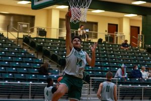 As he jumps for a basket, freshman Jaxson Ford warms up before the game. This year marks Ford's first  on varsity, and he is the only freshman on the team. Ford played as a power forward during the scrimmage.