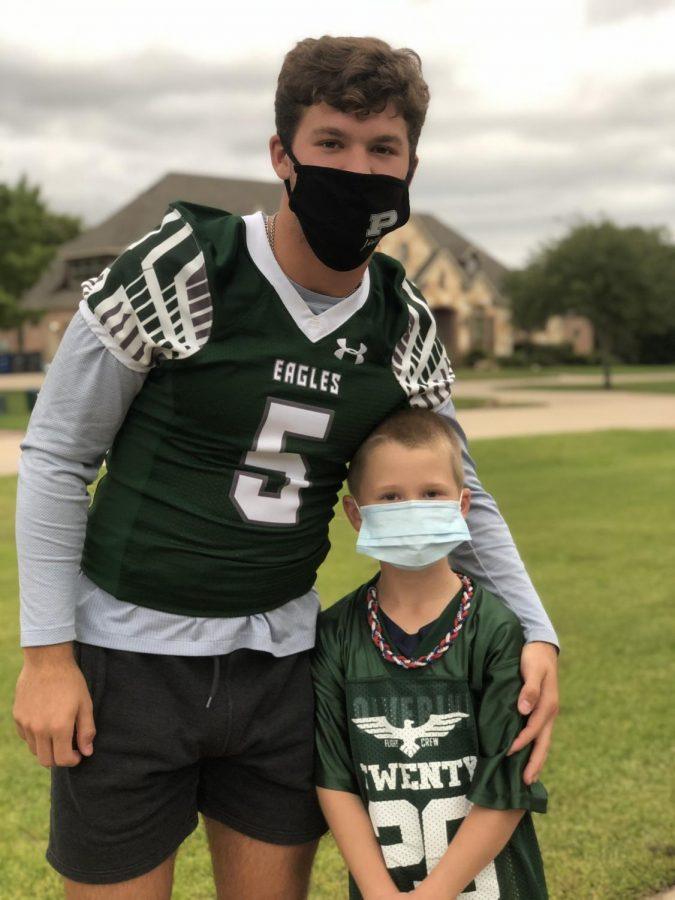 After visiting his Flight Crew buddy, senior Jackson Berry stands with second grader Eli Mahan. Mahan often goes to support Berry at his home football games. Having young men in our community serve as role models is incredible, government teacher Irish Mahan, Eli Mahans mom said. My family is thankful for this program and the joy it has brought to our son.