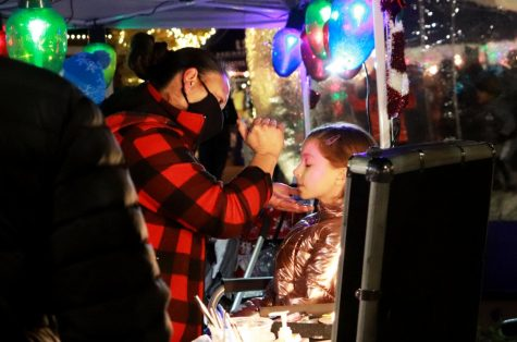 "Sitting still for the artist, a young girl receives a holiday face painting. The annual ""Christmas on the Square"" festival in downtown Celina, Texas was held Dec. 2. The event featured festivities, including horse-drawn carriages, bounce houses, Christmas carolers and face painting."