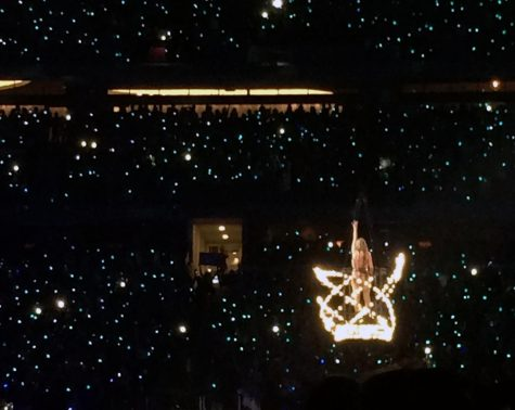 Standing on a platform above the crowd, Taylor Swift performs her song