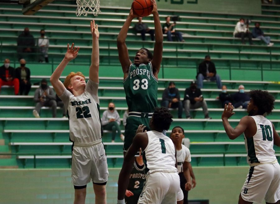 Arms raised for a dunk, senior Brandon Sofi reaches for the basket while Berkner defenders . The Eagles played the Richardson Berkner Rams on Tuesday, Dec. 1 at the Berkner Arena. The boys came off with a 61-44 win.