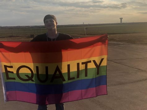 Sophomore Taylor Holcomb stands with his equality pride flag at his home. This column discusses how the media impacts LGBTQ+ viewers.