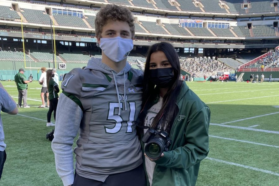 Attending the Eagle football playoff, sophomores Evan Bish and Neena Sidhu stand on the sidelines. Sidhu took pictures for Eagle Nation Online, and Bish held signs to help the offense on the field. Throughout the break, they both attended the Eagles playoff games.