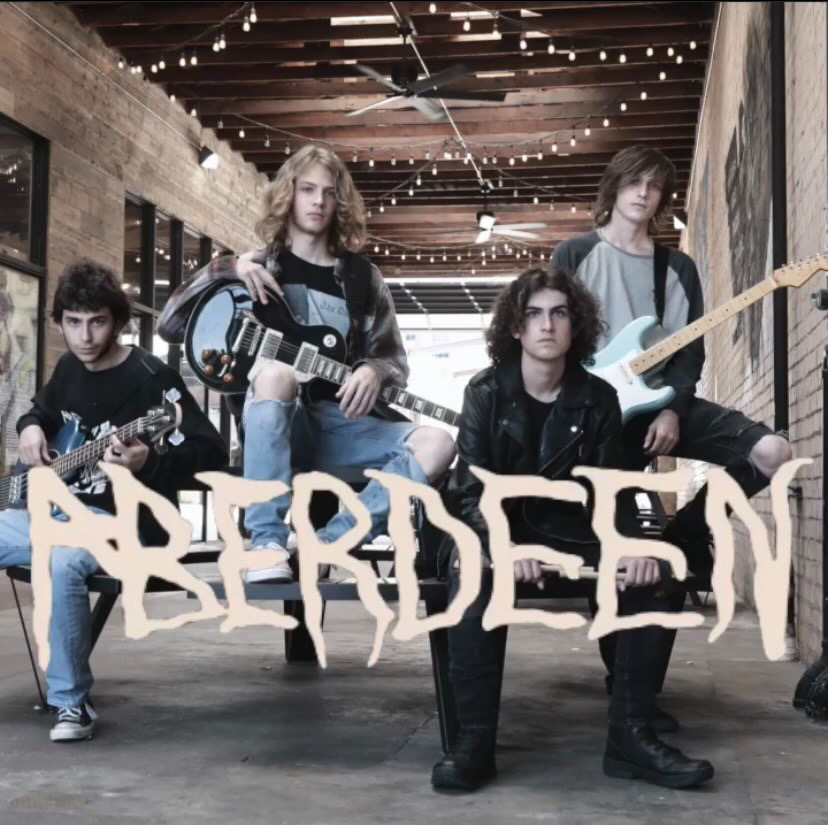 Sitting on a bench, members of Aberdeen position themselves with their instruments. Aberdeen members present themselves as a classic rock band with a mission.
