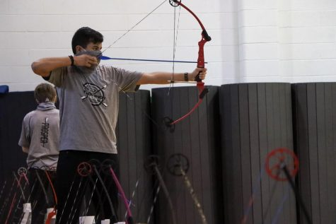 "As he lines up the shot, junior Sam Sidhu steadies his bow. Sidhu competed in the national competition during his freshman year, but his sophomore year nationals were cancelled due to COVID-19. ""I enjoy archery, and I keep trying to get better every practice,"" Sidhu said. ""I hope the rest of our season continues normally."""