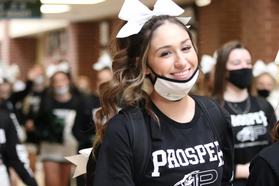 Headed to the buses, senior Genesis Gibson walks down the hall during a cheer send off. The Prosper High School cheerleaders have been practicing for the UIL Cheer competition. The team took sixth place at the 2021 6A State Championship.
