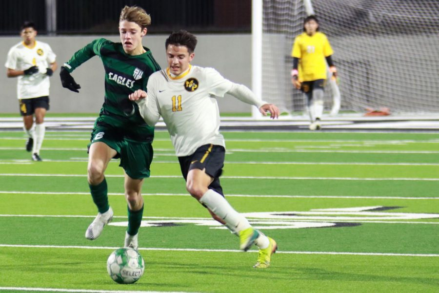 In an attempt to get away from his opponent, senior Cooper Olsen chases after the ball. The boys soccer team took on Mt. Pleasant and lost 1-2. They will face off against Rockwall Jan. 8 at 2 p.m. at Children's Health Stadium.