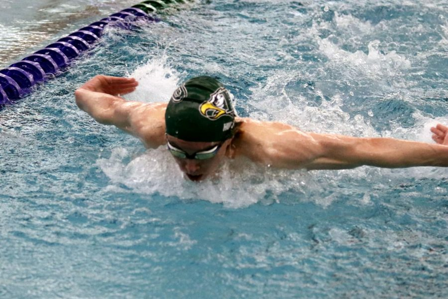 At the Jan. 13 meet, in the first lap of his 200-yard individual medley, senior Justice Hunt dives in ahead of the other swimmers. Hunt also swam the 200-yard medley relay, 100-yard freestyle, and the 200-yard freestyle relay events. He will be competing at state in the 200-yard freestyle and 100-yard freestyle.