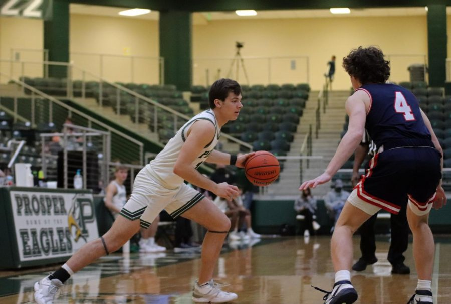 Looking to go around his opponent, senior Neal Utrup lunges past No. 4 Bronco Tate Stevens. Both Utrup and Stevens play as shooting guards for their teams. The Broncos are ranked fifth in district.