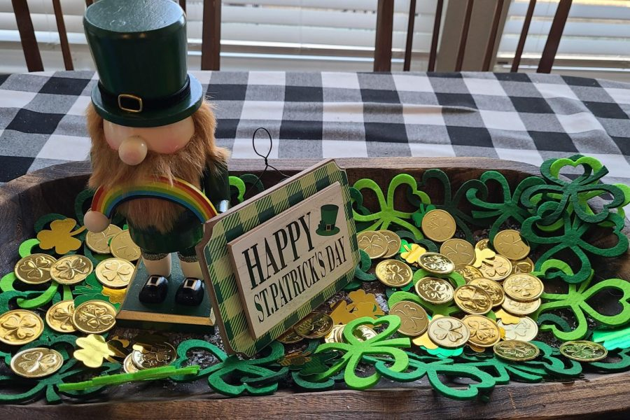 Sitting atop a dinner table, St.Patrick's Day decorations display the colorful excitement brought about by the holiday. St. Patrick's Day is celebrated every year on March 17. The most common symbols of St.Patrick's Day pictured in the photo are shamrocks, gold coins and a leprechaun.