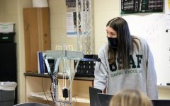 Watching her self-made bridge be tested by a machine applying force, junior Abigail Griffith watches as she reaches the top three placement of all competitors.