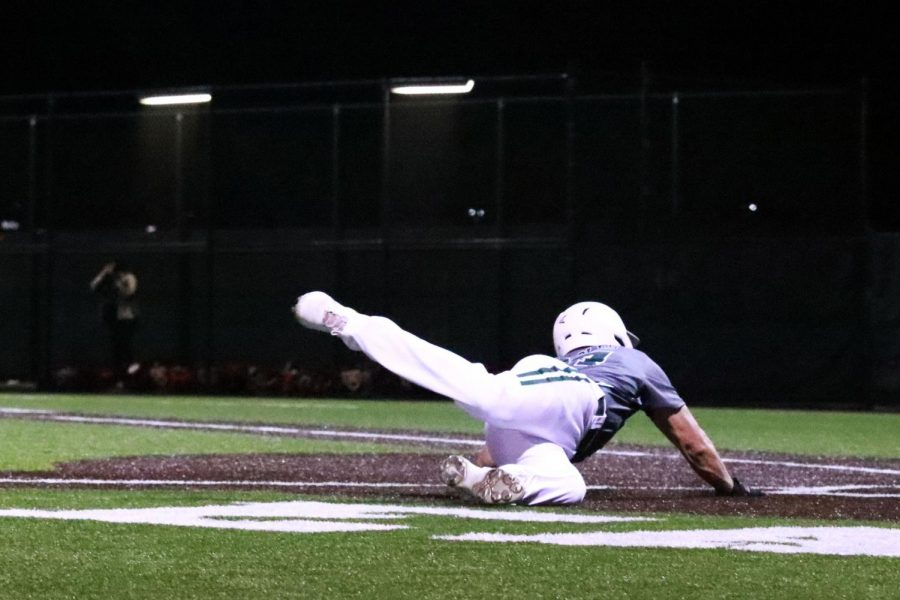 Sliding into first base, Jacob Devenney completes a run.