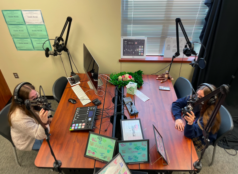 "Checking their microphones, junior Morgan Reese and sophomore Gianna Galante prepare to record the first episode of ""Astro Hour."" In this episode, Reese and Galante discuss natal astrology. Reese analyzes Galante"