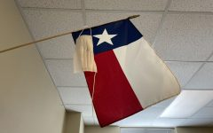 Broken and unworn, a mask hangs beside the Texas flag. Governor Greg Abbott passed an executive order March 2 lifting the mask mandate and allowing businesses to open to full capacity.