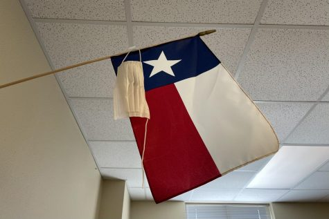"Broken and unworn, a mask hangs beside the Texas flag. Governor Greg Abbott passed an executive order March 2 lifting the mask mandate and allowing businesses to open to full capacity. ""With this executive order, we are ensuring that all businesses and families in Texas have the freedom to determine their own destiny,"" Abbott said."