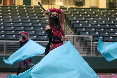 "Spinning her flag, freshman Madeline Ashton performs with the junior varsity Winter Guard. The show featured rifle and flag routines as well as chair choreography. The team spun to the song ""Vogue"" by Madonna."