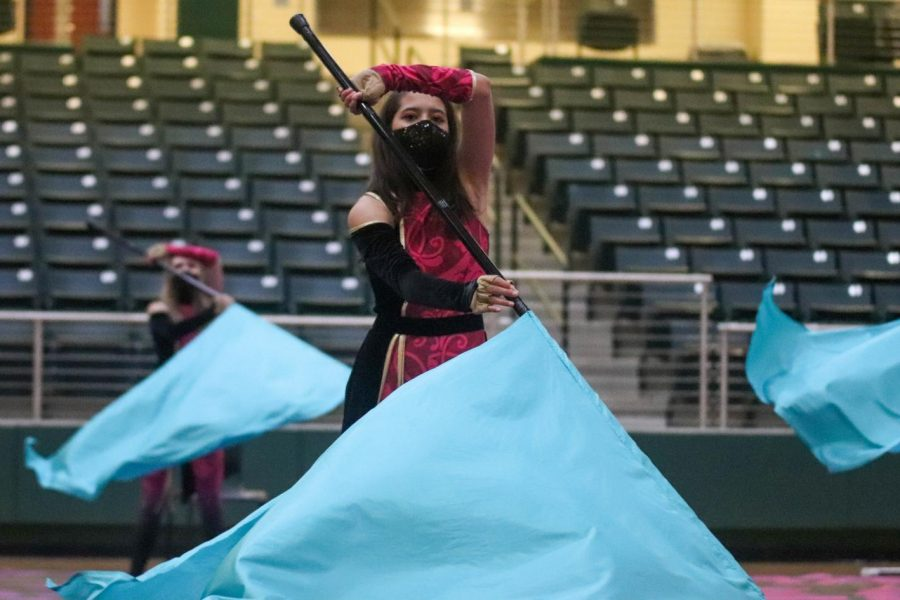 Spinning her flag, freshman Madeline Ashton performs with the junior varsity Winter Guard. The show featured rifle and flag routines as well as chair choreography. The team spun to the song